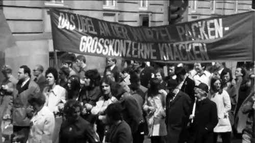 """""""Das Übel an der Wurzel packen - Großkonzerne knacken"""". Transparent bei einer Demonstration 1969 (Abbildung: Screenshot einer Dokumentation über die """"wilden"""" Streiks Ende der 1960er Jahre)"""